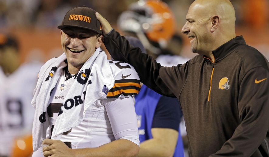 Cleveland Browns head coach Mike Pettine, right, pats quarterback Johnny Manziel on the head as they leave the field at halftime of a preseason NFL football game against the Chicago Bears, Thursday, Aug. 28, 2014, in Cleveland. (AP Photo/Tony Dejak)