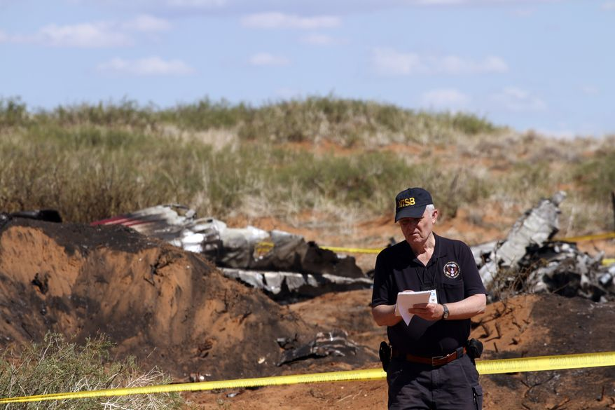 National Transportation Safety Board investigator Tom Latson takes notes in front of the wreckage from a twin engine aircraft in Las Cruces, N.M., Thursday, Aug. 28,  2014. Four people died when the medical transport airplane that was transporting a cancer patient to Phoenix, Arizona, crashed and burst into flames shortly after takeoff from Las Cruces Airport Wednesday. (AP Photo/Juan Carlos Llorca)