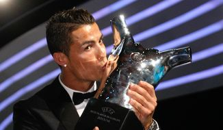 Named the best player of the year, Real Madrid Portuguese forward Cristiano Ronaldo, kisses his trophy during the UEFA Champions League draw, at the Grimaldi Forum, in Monaco, Thursday, Aug. 28, 2014. (AP Photo/Claude Paris)