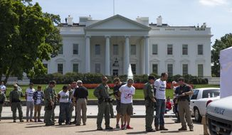 Demonstrators are lined up outside the White House in Washington, Thursday, Aug. 28, 2014, as they are being arrested during a protest on immigration reform. With impeachment threats and potential lawsuits looming, President Barack Obama knows whatever executive actions he takes on immigration will face intense opposition. So as a self-imposed, end-of-summer deadline to act approaches, Obama's lawyers are carefully crafting a legal rationale they believe will withstand scrutiny and survive any court challenges, administration officials say. (AP Photo/Evan Vucci)