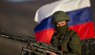 ** FILE ** A pro-Russian soldier is back dropped by Russia flag while manning a machine-gun outside an Ukrainian military base in Perevalne, Ukraine, Saturday, March 15, 2014. (Associated Press)