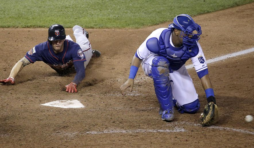 Minnesota Twins' Jordan Schafer slides home past Kansas City Royals catcher Salvador Perez to score on a two-run double by Brian Dozier during the 10th inning of a baseball game against the Kansas City Royals Thursday, Aug. 28, 2014, in Kansas City, Mo. The Twins won 11-5. (AP Photo/Charlie Riedel)