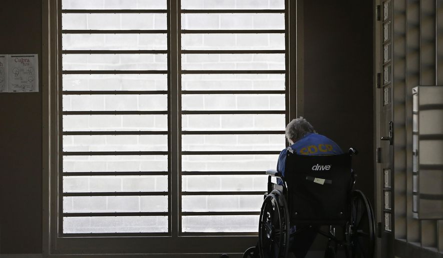 FILE --  In this July 24, 2014 file photo,   an inmate sits by a window at the mental health unit at the California Department of Corrections and Rehabilitation's Stockton Health Facility in Stockton, Calif. In an agreement filed in U.S. District Court in Sacramento,  Friday, Aug. 29, state corrections official have agreed to shift mentally ill inmates into specialized housing units instead of placing them in the same isolation units as are used for other inmates, Friday, Aug. 29.(AP Photo/Rich Pedroncelli, file)