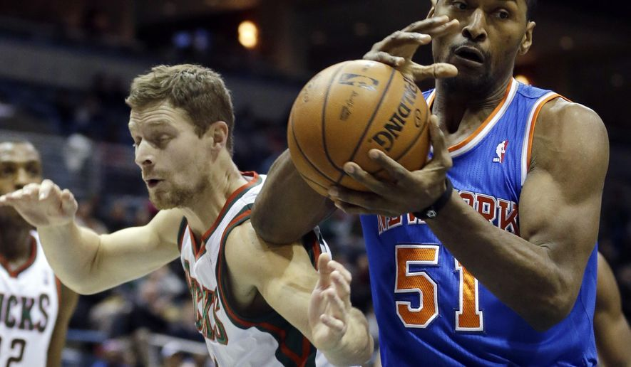 FILE - In this Wednesday, Dec. 18, 2013 file photo, Milwaukee Bucks' Luke Ridnour, front left, and New York Knicks' Metta World Peace (51) go after a rebound during the first half of an NBA basketball game, in Milwaukee. Manny Pacquiao has expressed interest in recruiting former NBA All Star Metta World Peace to the Filipino boxing champion's newest venture -  professional basketball. (AP Photo/Morry Gash, File)