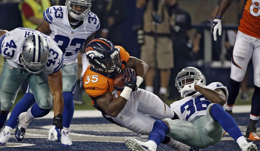 Denver Broncos running back Kapri Bibbs (35) fights his way against Dallas Cowboys' Ahmad Dixon (36), Keith Smith (43) and Ryan Smith (33) into the end zone for a touchdown in the second half of a NFL preseason football game, Thursday, Aug. 28. 2014, in Arlington, Texas. (AP Photo/Brandon Wade)