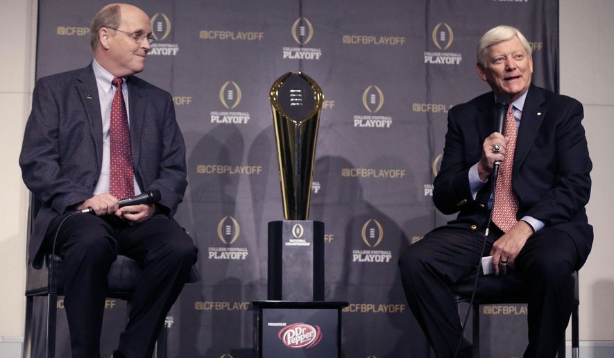 College Football Playoff executive director Bill Hancock, left, looks on as Cotton Bowl president Tommy Bain speaks during a news conference about fan events planned for the College Football National Championship game Friday, Aug. 29, 2014, in Arlington, Texas.  The pair announced a weekend of events leading up to the Monday, Jan. 12, 2015, game to be held at the Dallas Cowboys home stadium. (AP Photo/LM Otero)