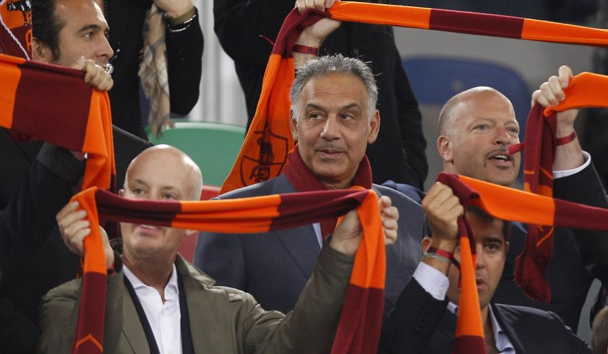"""FILE - In this April 8, 2013 file photo, AS Roma soccer club president James Pallotta, center, follows a Serie A soccer match between AS Roma and Lazio at Rome's Olympic stadium. For Italian football fans, merely mentioning the word """"scudetto"""" _ league title _ in association with a favorite club is considered tabu. The theory goes that it's better left unsaid until your squad actually raises the trophy. Yet recently, the word has begun popping up in animated discussions inside Rome's myriad coffee bars and impassioned sports-talk radio stations. The talk, and not only in the capital, is that Roma can put together a serious challenge for the Serie A title this season. Three years after takeover by US owners, Roma is expected to contend for the Serie A title.  (AP Photo/Alessandra Tarantino, file)"""