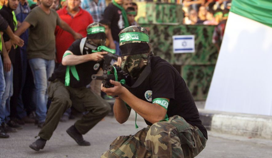 ** FILE ** Members of Hamas show off weapons as Palestinians join a celebration organized by Hamas in the West Bank city of Nablus, on Friday, Aug. 29, 2014. (Associated Press)