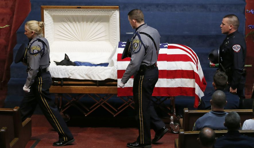 Police officers file past the casket of Oklahoma City police canine officer K-9 Kye during funeral services in Oklahoma City, Thursday, Aug. 28, 2014. K-9 Kye died Aug. 25 after being stabbed by a burglary suspect on Aug. 24. K-9 Kye died Aug. 25 after being stabbed by a burglary suspect on Aug. 24. (AP Photo/Sue Ogrocki)