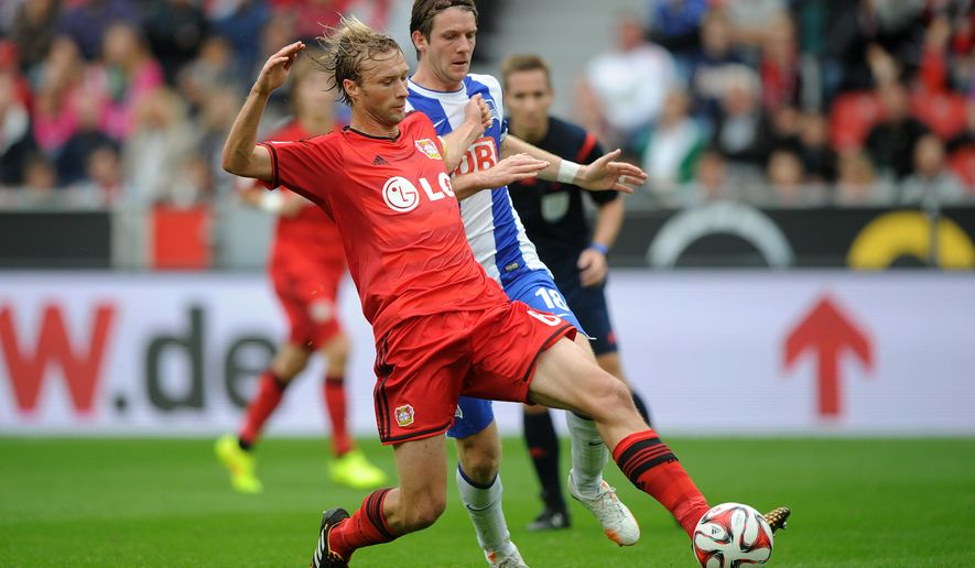 Leverkusen's Simon Rolfes, left, challenges for the ball with  Berlin's Peter Niemeyer during the German Bundesliga soccer match between Bayer Leverkusen and Hertha BSC Berlin in Leverkusen, western Germany, Saturday Aug. 30, 2014. (AP Photo/dpa,Jonas Guettler)