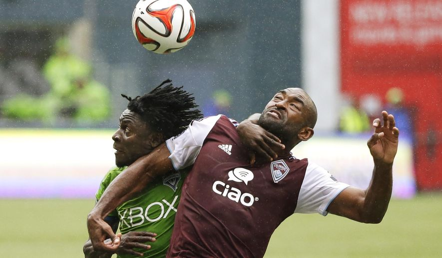 Seattle Sounders' Obafemi Martins, left, and Colorado Rapids' Marvell Wynne battle for a header in the second half of an MLS soccer match, Saturday, Aug. 30, 2014, in Seattle. The Sounders defeated the Rapids 1-0. (AP Photo/Ted S. Warren)