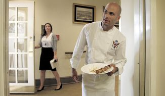 In this photo taken Aug. 9, 2010, White House chef Sam Kass holds a plate of seafood from the Gulf of Mexico that had been prepared at the White House by members of the New Orleans Saints football team in Washington. (AP Photo/Pablo Martinez Monsivais) ** FILE **