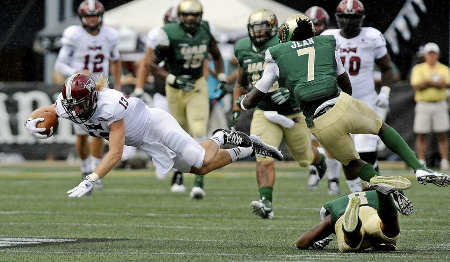UAB safety Jay Davis (8) and cornerback Jimmy Jean (7) trip up Troy wide receiver K.D. Edenfield (13) during the second half an NCAA college football in Birmingham, Ala., Saturday, Aug. 30, 2014. UAB won 48-10. (AP Photo/The (Troy) Messenger, Thomas Graning)