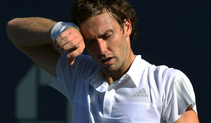 Ernests Gulbis, of Latvia, wipes sweat from his brow between points against Dominic Thiem, of Austria, during the second round of the 2014 U.S. Open tennis tournament, Friday, Aug. 29, 2014, in New York. (AP Photo/John Minchillo)