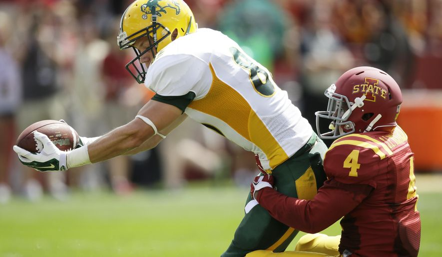 North Dakota State wide receiver Zach Vraa tries to break a tackle by Iowa State defensive back Sam E. Richardson (4) during the first half of an NCAA college football game, Saturday, Aug. 30, 2014, in Ames, Iowa. (AP Photo/Charlie Neibergall)