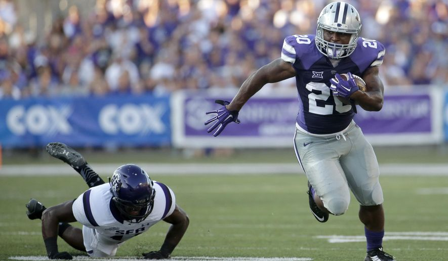 Kansas State running back DeMarcus Robinson (20) gets past Stephen F. Austin defensive back Patrick Martin (14) as he runs the ball during the first half of an NCAA college football game Saturday, Aug. 30, 2014, in Manhattan, Kan. (AP Photo/Charlie Riedel)