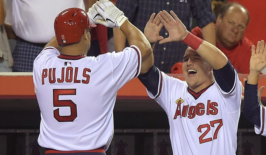 Los Angeles Angels' Albert Pujols, left, is congratulated by Mike Trout after hitting a solo home run during the seventh inning of a baseball game against the Oakland Athletics, Friday, Aug. 29, 2014, in Anaheim, Calif. (AP Photo/Mark J. Terrill)