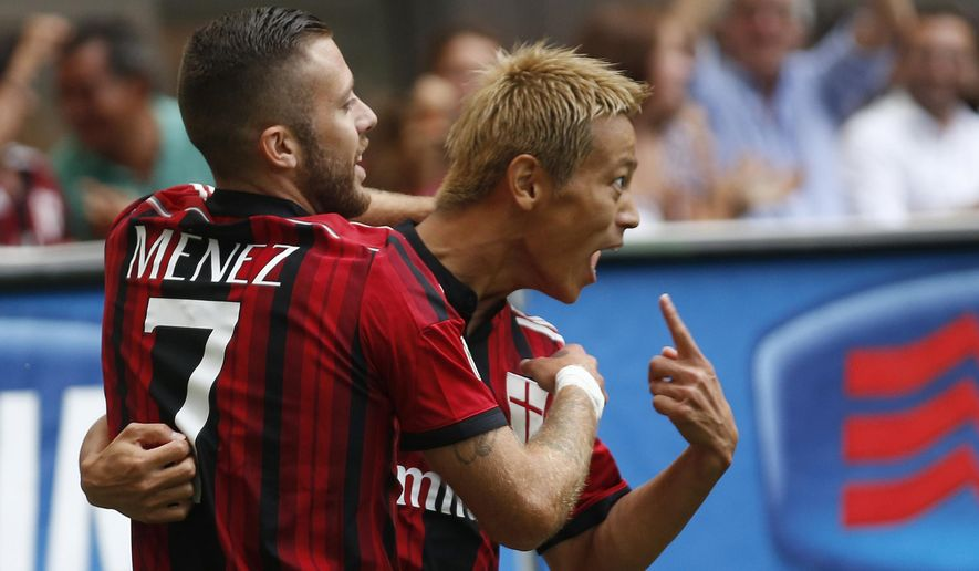 AC Milan forward Keisuke Honda, of Japan, right, celebrates with his teammate Jeremy Menez of France after scoring during a Serie A soccer match between AC Milan and Lazio, at the San Siro stadium in Milan, Italy, Sunday, Aug. 31, 2014. (AP Photo/Luca Bruno)