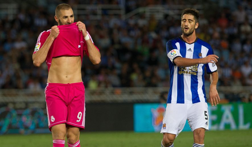 Real Madrid's Benzema, left, lifts his shirt during a Spanish La Liga soccer match between Real Madrid and Real Sociedad at the Anoeta stadium in San Sebastian, Spain, Sunday, Aug. 31, 2014. (AP Photo/Jose Ignacio Unanue)