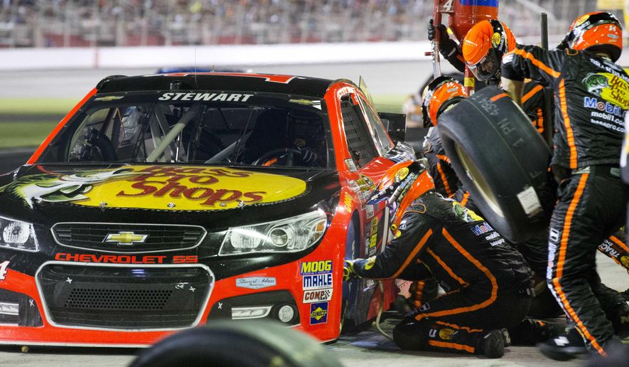 Sprint Cup Series driver Tony Stewart (14) gets a tire during an NASCAR Sprint Cup auto race at Atlanta Motor Speedway Sunday, Aug. 31, 2014, in Hampton, Ga. Stewart was racing for the first time since being involved in a fatal dirt track incident in N.Y.   (AP Photo/Bryn Anderson)