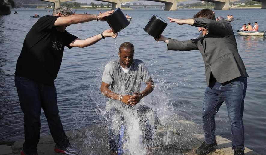 Two-time Grammy award winning rapper and a founding member of the Fugees, Pras Michel, gets doused by his friends for the ALS Ice Bucket Challenge, Sunday, Aug. 31, 2014 in Pyongyang, North Korea. The American rapper and documentary filmmaker said he wanted to join in the immensely popular charity challenge and thought of Pyongyang where the ice bucket craze is unknown, would be the perfect place to do it. (AP Photo/Wong Maye-E)