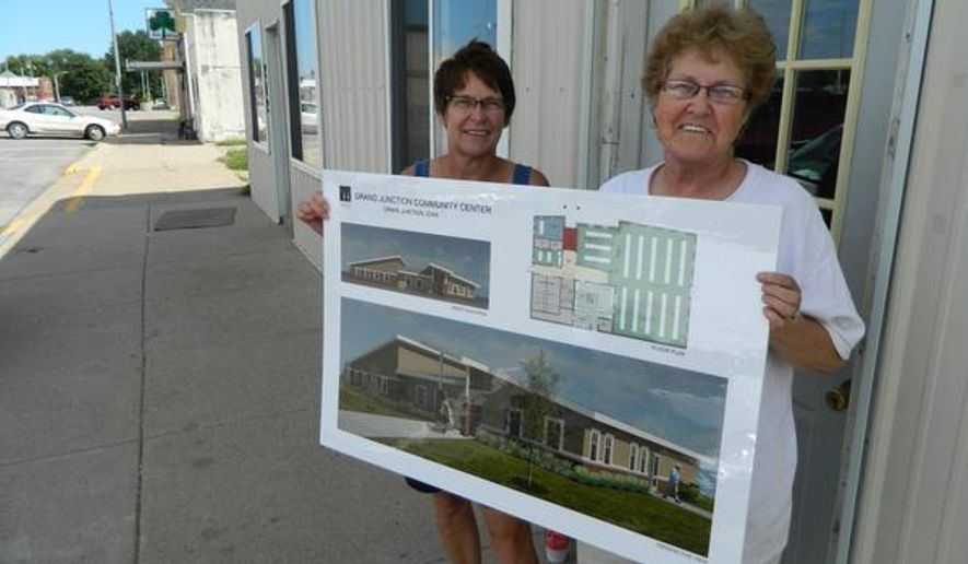 "Diane ""the pusher"" Wise, left, stands in downtown Grand Junction next to Shirley Herrick. Wise, of rural Jefferson, has spearheaded an effort to build a new community center in the town of 800, where her late husband was raised, as a means to spark revival. Here the two women stand in front of the existing, gutted community center and hold a sign that shows a conceptual drawing of what they hope is built in 2015. (AP Photo/The Des Moines Register, Kyle Munson)  MAGS OUT, TV OUT, NO SALES, MANDATORY CREDIT"