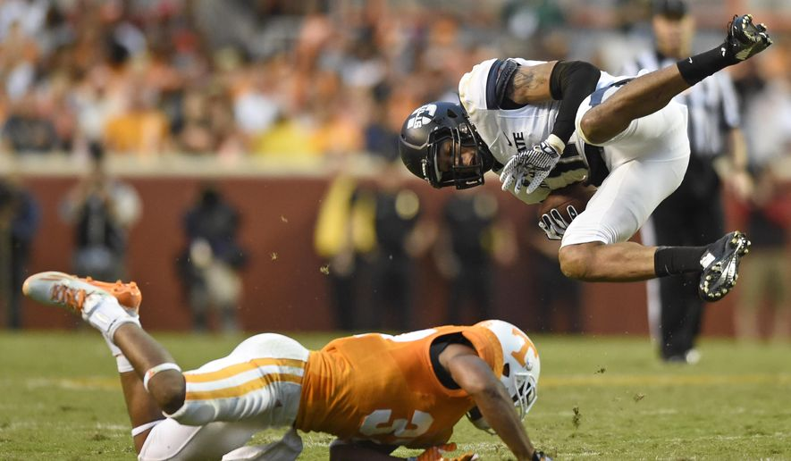 Tennessee defensive back Brian Randolph,  bottom, upends Utah State wide receiver Brandon Swindall (11) during the first half of their NCAA college football game at Neyland Stadium, Sunday, Aug. 31, 2014 in Knoxville, Tenn.  (AP Photo/Knoxville News Sentinel, Saul Young)
