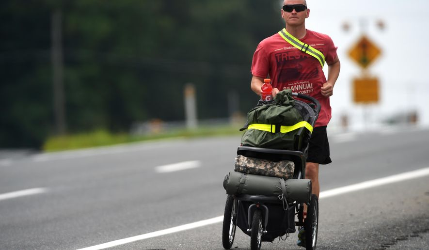 ADVANCE FOR RELEASE SUNDAY, AUG. 31, 2014, AT 9:00 A.M. EDT. - In this Aug. 20, 2014 photo, Tony Smith runs on Route 460 from Bedford to Lynchburg, Va., with his belongings packed in his son's old stroller. Smith quit his job of 12 years as a mail carrier in Pulaski to run across the country in hopes of raising awareness for suicide prevention. (AP Photo/News & Daily Advance, Autumn Parry)