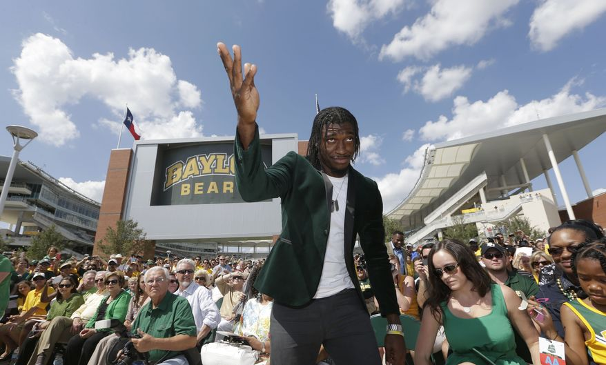 Washington Redskins quarterback Robert Griffin III acknowledges fans as he heads to unveil a bronze statute of himself outside the new McLane Stadium before an NCAA college football game between SMU and Baylor Sunday, Aug. 31, 2014, in Waco, Texas. Griffin won the Heisman Trophy when he played at Baylor. (AP Photo/LM Otero)