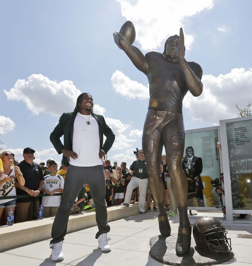 Washington Redskins quarterback Robert Griffin III looks at a bronze statute of himself after it was unveiled outside the new McLane Stadium before an NCAA college football game between SMU and Baylor Sunday, Aug. 31, 2014, in Waco, Texas. Griffin won the Heisman Trophy when he played at Baylor. (AP Photo/LM Otero)