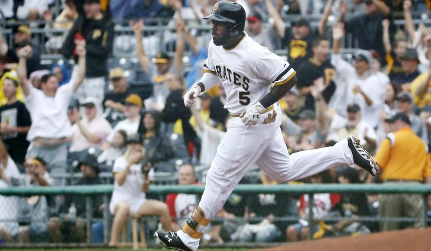 Pittsburgh Pirates' Josh Harrison (5) rounds first after hitting a solo home run off Cincinnati Reds starting pitcher Johnny Cueto during the first inning of a baseball game in Pittsburgh, Sunday, Aug. 31, 2014. (AP Photo/Gene J. Puskar)