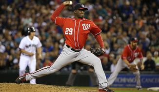 With a man on first, Washington Nationals closing pitcher Rafael Soriano throws against the Seattle Mariners in the ninth inning of a baseball game, Saturday, Aug. 30, 2014, in Seattle. Soriano picked up a save as the Nationals defeated the Mariners 3-1. (AP Photo/Ted S. Warren)
