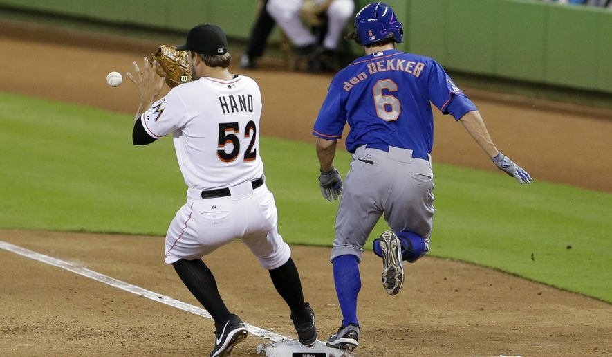 New York Mets' Matt den Dekker (6) is safe at first as Miami Marlins relief pitcher Brad Hand (52) waits for the throw during the fourth inning of a baseball game, Monday, Sept. 1, 2014 in Miami. (AP Photo/Wilfredo Lee)
