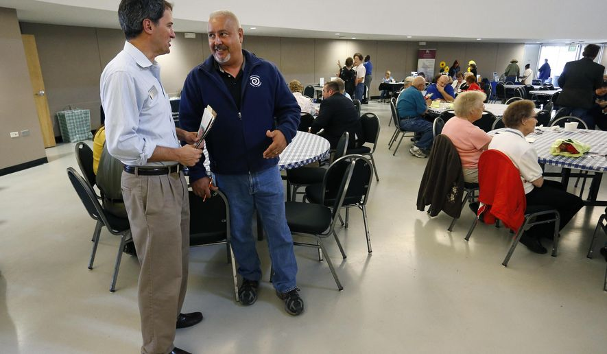 In this July 31, 2014 photo, Democratic congressional candidate Andrew Romanoff, left, talks with county fair attendees during a campaign visit in Brighton, Colo. Romanoff  is running against against three-term Republican Rep. Mike Coffman. (AP Photo/Brennan Linsley)