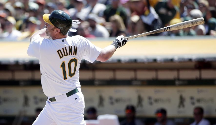 Oakland Athletics' Adam Dunn hits a two-run home run against the Seattle Mariners during the first inning of a baseball game on Monday, Sept. 1, 2014, in Oakland, Calif. (AP Photo/Marcio Jose Sanchez)