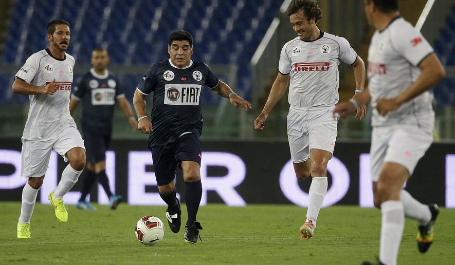 Diego Armando Maradona controls the ball as Diego Simeone, left, Gabriel Heinze, second right, and Ivan Zamorano watch him, during an inter-religious soccer match for peace, supported by Pope Francis to promote the dialogue and peace among different religions, at Rome's Olympic Stadium, Monday, Sept. 1, 2014. (AP Photo/Gregorio Borgia)