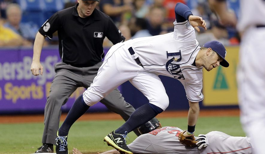 Tampa Bay Rays third baseman Evan Longoria stretches to tag out Boston Red Sox's Xander Bogaerts (2) at third base on a stolen base attempt during the fifth inning of a baseball game Monday, Sept. 1, 2014, in St. Petersburg, Fla. Making the call is umpire Mike Estabrook. (AP Photo/Chris O'Meara)