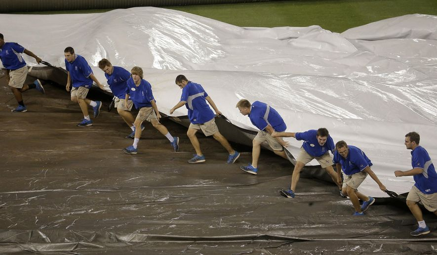 Members of the grounds crew  pull the tarp on the field during a rain delay in the 10th inning of a baseball game between the Kansas City Royals and the Cleveland Indians Sunday, Aug. 31, 2014, in Kansas City, Mo. (AP Photo/Charlie Riedel)