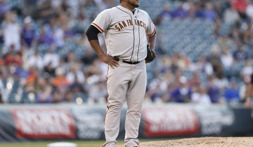 San Francisco Giants relif pitcher Jean Machi reacts after giving up a two-run home run to Colorado Rockies' pinch-hitter Ben Paulsen in the seventh inning of the Rockies' 10-9 victory in a baseball game in Denver on Monday, Sept. 1, 2014. (AP Photo/David Zalubowski)