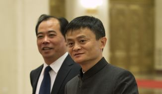In this June 11, 2014 photo, Jack Ma, right, founder and executive chairman of Alibaba Group arrives for a meeting at the Great Hall of the People in Beijing, China. Foreigners who want to buy Alibaba Group shares in the Chinese e-commerce giant's U.S. public offering will need to get comfortable with an unusual business structure. (AP Photo/Andy Wong)