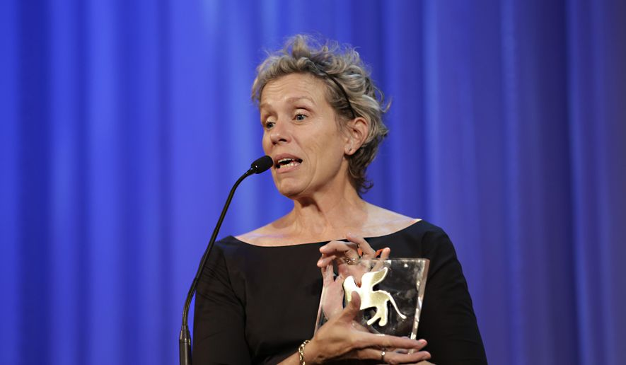 Actress Frances McDormand holds the Personal Tribute to Visionary Talent Award she just received at the 71st edition of the Venice Film Festival, in Venice, Monday, Sept. 1, 2014. (AP Photo/Andrew Medichini)
