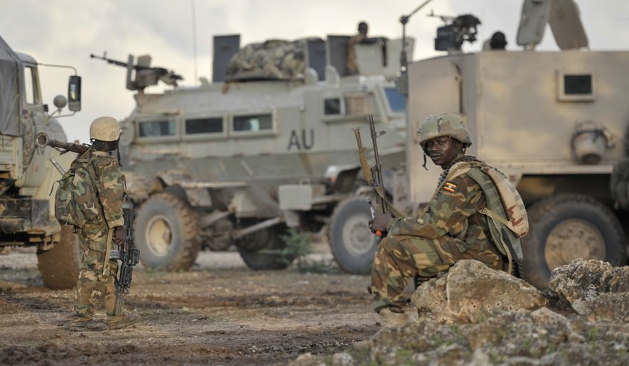"""In this photo taken Sunday, Aug. 31, 2014 and provided by the African Union Mission to Somalia (AMISOM) Monday, Sept. 1, 2014, African Union (AU) soldiers from Uganda rest in the town of Kurtunwarey in Somalia. Somali government and AU troops have been engaging al-Shabab militants as part of their military offensive dubbed """"Indian Ocean"""" aiming to oust al-Shabab from its last major hideouts in the southern parts of the Horn of Africa nation. (AP Photo/AMISOM, Tobin Jones)"""