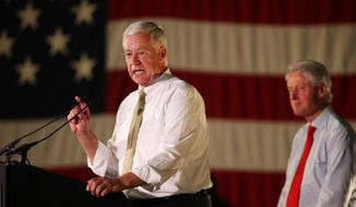 Rep. Mike Michaud, D-Maine, left, joined by Former President Bill Clinton, right, speaks Tuesday, Sept. 2, 2014 in Portland, Maine at a campaign rally for Michaud's campaign for governor. (AP Photo/Joel Page)