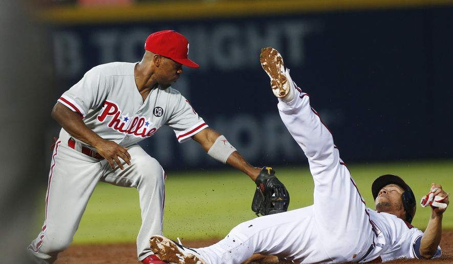 Atlanta Braves' Andrelton Simmons (19) is out at second attempting to steal as Philadelphia Phillies shortstop Jimmy Rollins applies the tag in the third inning of a baseball game Tuesday, Sept. 2, 2014, in Atlanta. (AP Photo/John Bazemore)