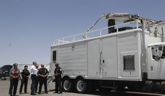 **FILE** President Barack Obama and Homeland Security Secretary Janet Napolitano examine an x-ray vehicle as they tour the Bridge of America Cargo Facility in El Paso, Texas, on May 10, 2011, during their visit to the U.S.-Mexico border. (Associated Press)