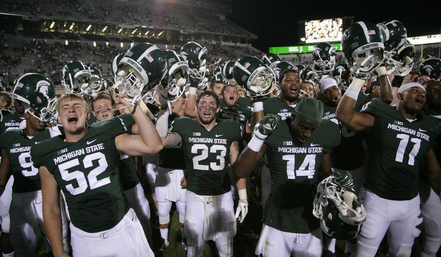 Michigan State players, including Taybor Pepper (52), Chris Frey (23), Tony Lippett (14), and Jamal Lyles (11), celebrate following a 45-7 win over Jacksonville State in an NCAA college football game, Friday, Aug. 29, 2014, in East Lansing, Mich. (AP Photo/Al Goldis)