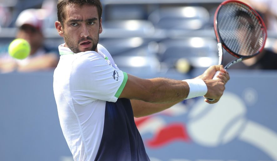 Gilles Simon, of France, returns a shot against Marin Cilic, of Croatia, during the fourth round of the 2014 U.S. Open tennis tournament, Tuesday, Sept. 2, 2014, in New York. (AP Photo/John Minchillo)