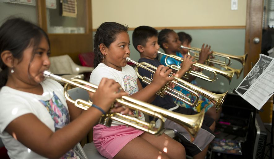 Arielle Dominguez, from left, Elizabeth Lopez, Andres Lopez, Azariah Wright and Katie Bella play their trumpets during a lesson offered by Harmony Project, a Los Angeles-based nonprofit that provides free music lessons to low-income students, Thursday, Aug. 28, 2014, in Los Angeles. A two-year study of dozens of schoolchildren from disadvantaged Los Angeles neighborhoods shows that music training changes the brain in ways that make it easier for youngsters to process sounds, according to results reported in Tuesday's edition of the journal Neuroscience. (AP Photo/Jae C. Hong)