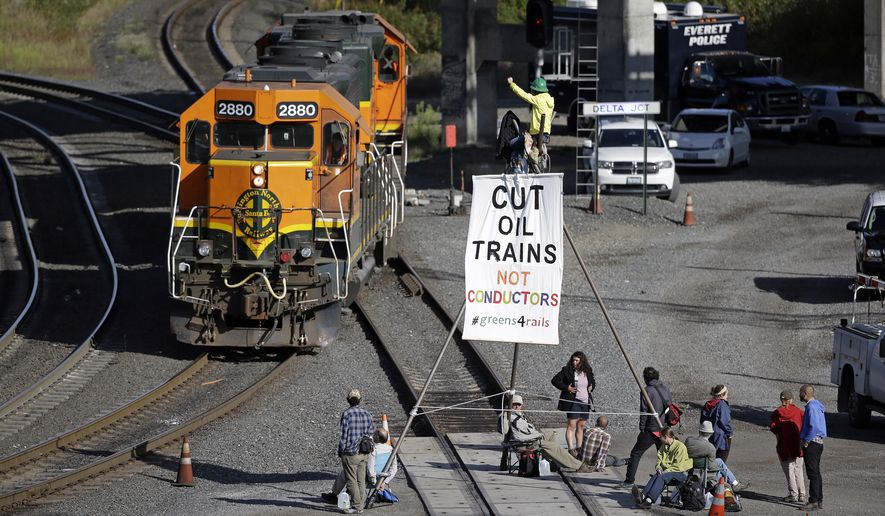Abby Brockway waves from atop a tripod erected on train tracks to a pair of engines passing on an adjacent track Tuesday, Sept. 2, 2014, in Everett, Wash. About a dozen demonstrators blocked the tracks at a Burlington Northern Santa Fe yard to protest oil and coal export terminals in the Northwest. (AP Photo/Elaine Thompson)