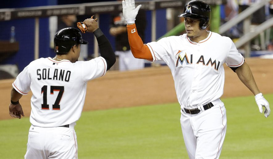 Miami Marlins' Giancarlo Stanton, right, is met at the plate by Donovan Solano (17) after scoring on a two-run home run hit by Stanton in the third inning during a baseball game against the New York Mets, Tuesday, Sept. 2, 2014, in Miami. (AP Photo/Lynne Sladky)
